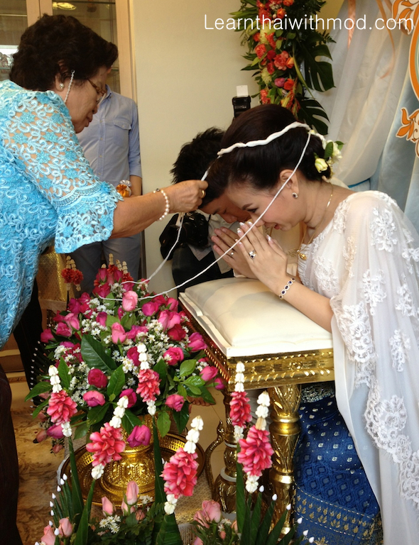 The bride's grandmother is putting the Mong Kol for the couple.